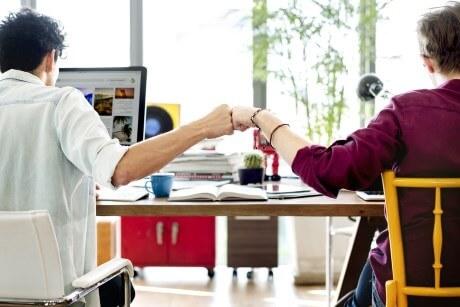 Zwei Innendienst Mitarbeiter freuen sich über gutes Teamwork